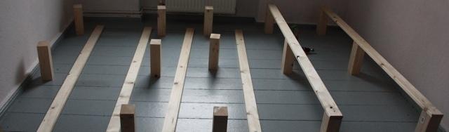 Verteilung der Holzblöcke und Längslatten für den Bau eines Familienbetts